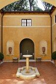 A fountain in the courtyard of a Mediterranean villa with a terracotta floor and a yellow facade