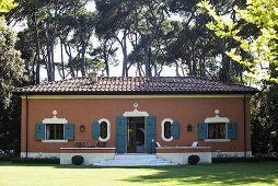 Mediterranean villa with a red brick facade and blue-gray shutters in a garden
