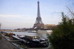 Sunny day in Paris - house boat docked on the bank looking across the Seine at the Eiffel tower