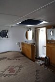 Cabin with a vanity and shower stall in a house boat