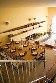 Blick von Treppe aufgedeckten Tisch im offenen Wohnzimmer eines Landhauses