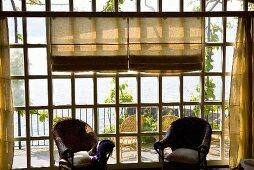 Sonniger Tag- Korbstühle vor Sprossenfenster mit Blick auf Terrasse und den See