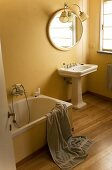 Ländliches Bad - Standwaschbecken mit Spiegel vor gelber Wand und graues Handtuch über Badewanne