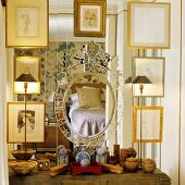A collection of pictures in gold frames in front of a mirror with various containers on the shelf