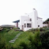 A newly built, white cubic house with a garden on the English coast