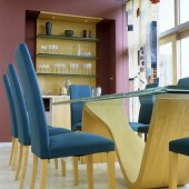 Blue upholstered chairs at a dining table with a curved wooden base and a shelf built into a red wall