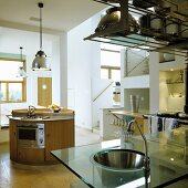An open-plan kitchen with a stainless steel sink set into a glass work surface and a round island counter