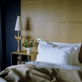Bed in front of a wood paneled wall and night stand with table lamp