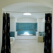 A bathroom with a vaulted ceiling - a view through an open curtain onto a bath in a niche with blue wall tiles