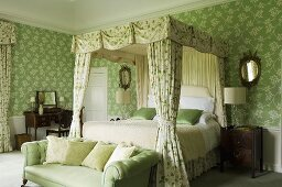An elegant country house-style bedroom with a green upholstered sofa at the foot of a four-poster bed with a canopy and floral, green wallpapered walls