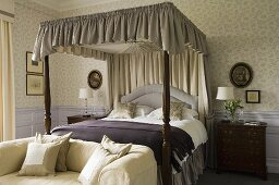 A bedroom in a country house with an upholstered sofa at the end of a four poster bed and a canopy with a gathered curtain