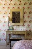 A table lamp on simple wall table standing against a floral papered wall in a bedroom
