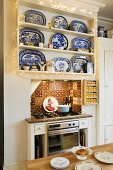 Blue and white dishes on a built-in kitchen shelf hung with a chain of lights and Oriental tiles decorating a niche where the gas oven stands
