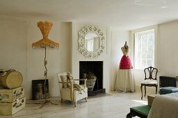 A white, sparsely decorated fireplace room - a floor lamp with a yellow shade and a tailor's dummy by the window wearing a dress