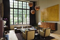 An art deco style armchair and a designer sideboard in front of studio windows with black frames