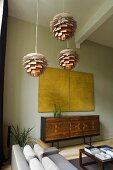 Bauhaus-style ceiling lamps and a yellow picture hanging above a designer sideboard