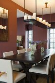 An elegant dining room with dark red walls and a hanging shelf with candles above a dark wooden table