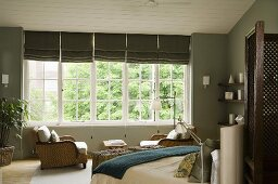 An elegant bedroom with grey wall and a double bed in front a bank of white-painted windows with grey blinds