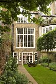 An English residential house with white transom windows and a sculpture in a turfed courtyard