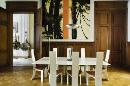 A wood panelled dining room in a villa with a white designer table and chairs