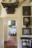 An antique Greek column capital above a door and view through an open door onto a dining room