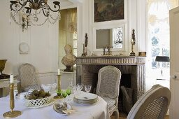 Candle holders and crockery on a table covered with a white table cloth and woven-back chairs in front of a fireplace