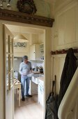 A view from a cloakroom through an open door into a white fitted kitchen where a man is cooking