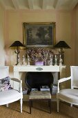 Baroque chairs and a foot stool in front of a white shelf and a table lamps with black shades