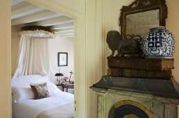 A view from a hallway into a country-style bedroom with a white double bed with a canopy