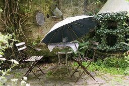 An old garden table with chairs and a parasol on a natural stone terrace in a rear courtyard