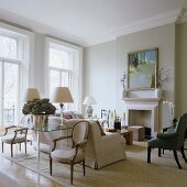 A classic English living room with grey wall and a light coloured sofa in front of a fireplace