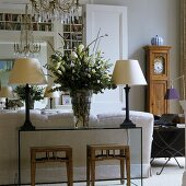 Table lamps with white shades and a bunch of lilies on a glass table with rustic stools and an antique grandfather clock