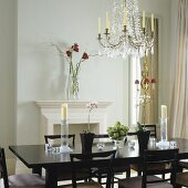 A dining room in an English apartment with a fireplace with an elegant black dining table and chairs with a crystal chandelier hanging from the ceiling