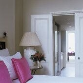 A view from a bedroom into a corridor - a table lamp with a light-coloured lamp shade next to a bed with pink cushions