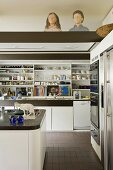 A white fitted kitchen with open shelving and wooden busts on the lowered ceiling