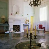 A fireplace room with a black and white tiled floor in a Mediterranean villa - a blue metal chair and an antique candle stick on a table