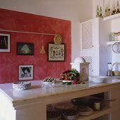 A Mediterranean kitchen - a marble surface on a white stone kitchen island in front of a sponged-painted red wall