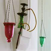 A water pipe in a white stone niche with coloured tea light holders hanging on either side