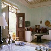 A living room in a Mediterranean house with a stone, upholstered seating corner and an open door with a view of the garden