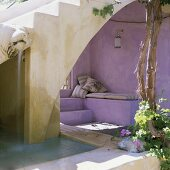 Mediterranean courtyard with a stone flight of steps and a lilac painted, upholstered niche
