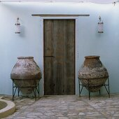 A Mediterranean courtyard - heavy amphorae in metal stands in front of a rustic wooden door on a natural stone floor