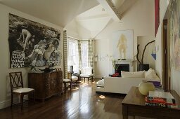 A mixture of styles in a living room with walnut parquet - an antique chest of drawers and a white, modern-style sofa