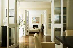A suite of rooms - open glass doors and continuous parquet floor in a dining room and a living room
