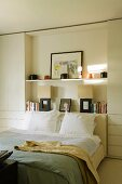 A white bedroom with a double bed in front of a self set into a wall niche
