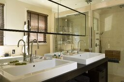 A designer bathroom with a mirrored wall and a black washstand with two white basins