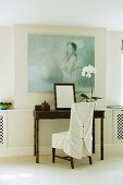 A bamboo table with a chair with a white cover against a wall hung with a picture