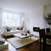 A white-painted designer living room with sofa in front of a window and a coffee table in front of a fireplace