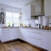 A corner of a white fitted kitchen with stainless steel handles and an integrated extractor hood