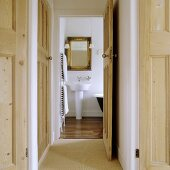 The hallway of an apartment with an open wooden door providing a view onto a designer wash basin and a golden-framed mirror