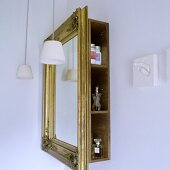 A bathroom corner - a mirror in a gold frame in front of a shelf with side opening and a pendant lamp with white glass shades